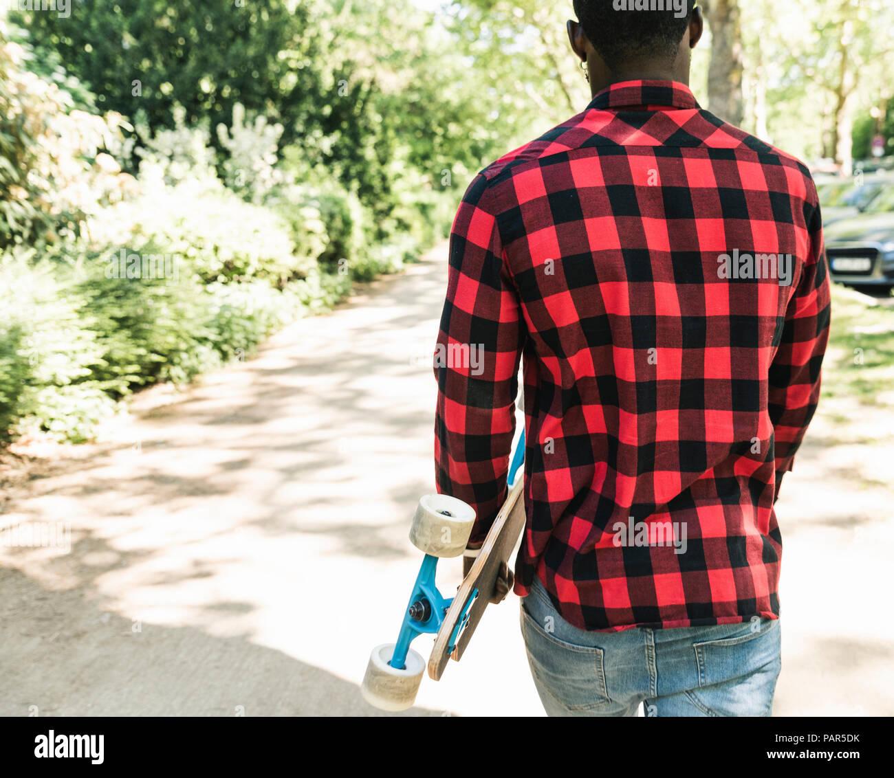 Cool joven con skateboard caminar en la ciudad. Imagen De Stock