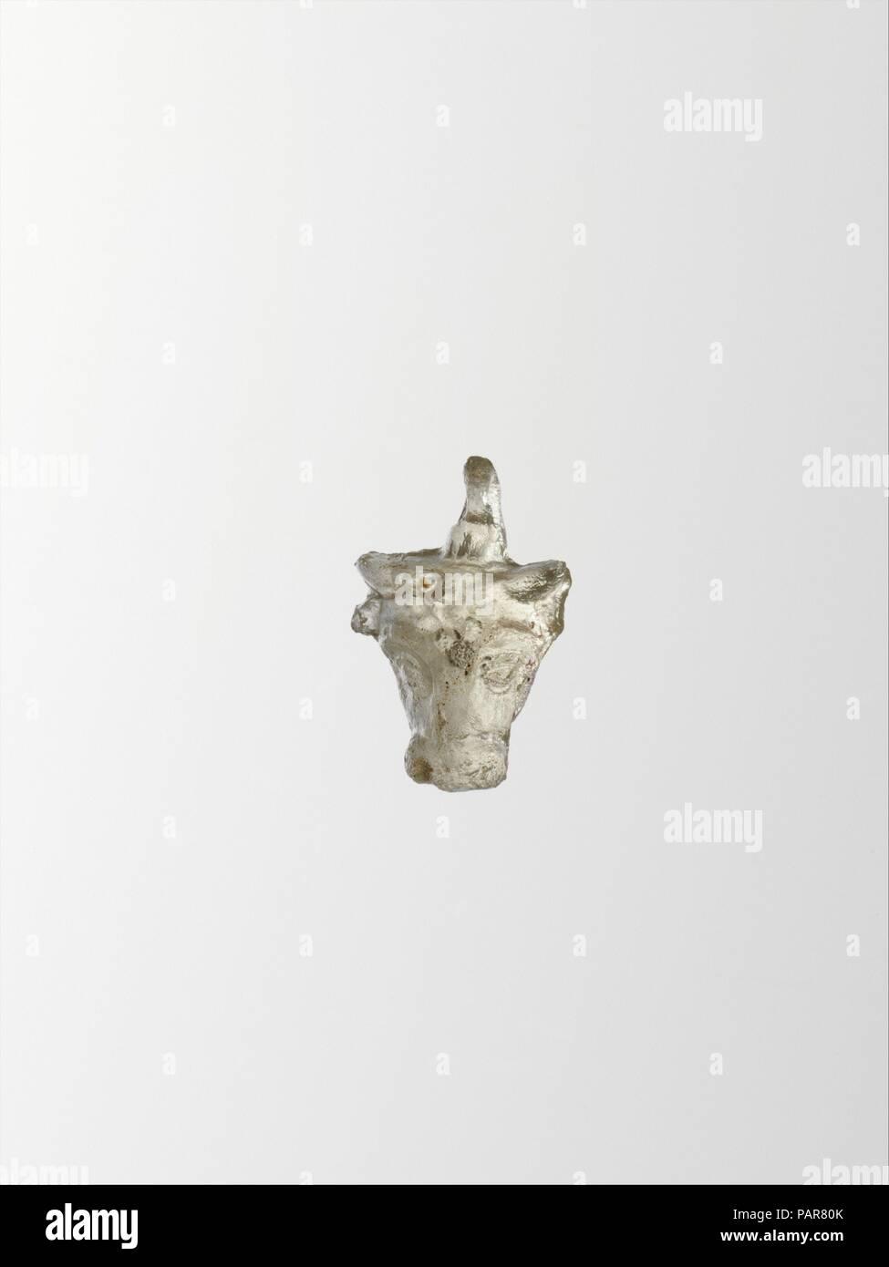 Colgante de Cristal en forma de cabeza de toro. Cultura: el griego, el Mediterráneo Oriental. Dimensiones: H.: 13/16. (2,1 cm). Fecha: finales de 2ª-1ª siglo A.C.. Incoloro. Sólido, vertical, colgante con marcas de molde, corriendo los costados y la parte superior de la cabeza y más de bucle; en la parte superior de la cabeza, un pequeño bucle; suspensión vertical plana con diminuto agujero central. Cabeza de Toro, con cuernos y orejas, cejas prominentes y ojos saltones; roseta de estrellas en la frente. Intacto pero desconchados alrededor de los bordes; algunas picaduras y tenues meteorización iridiscentes. Museo: Museo Metropolitano de Arte, Nueva York, Estados Unidos. Foto de stock