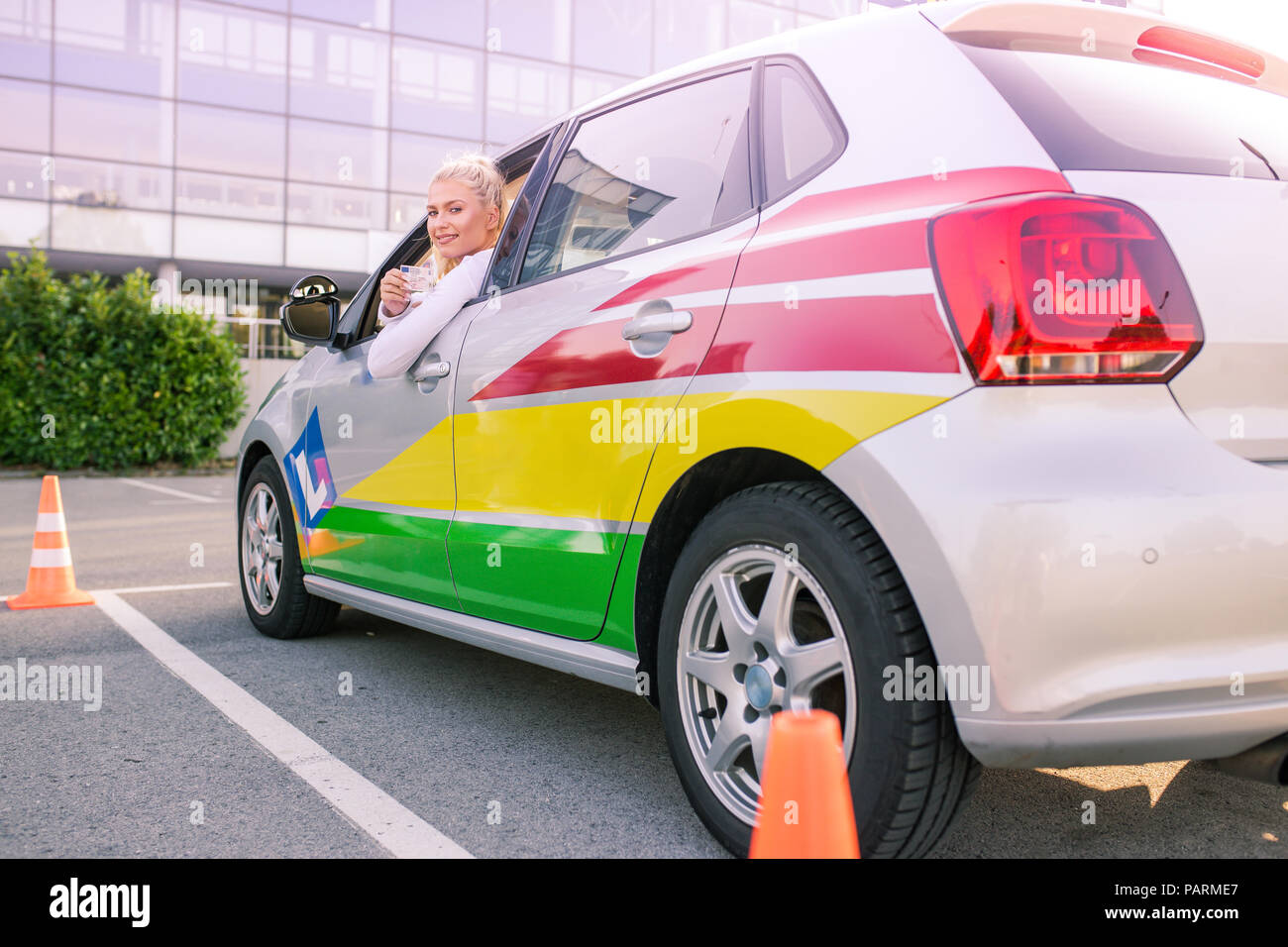 Escuela de conducción. Atractiva mujer joven mostrando con orgullo su carnet de conducir. Espacio libre para el texto. Copie el espacio. Los brillos de la lente Imagen De Stock