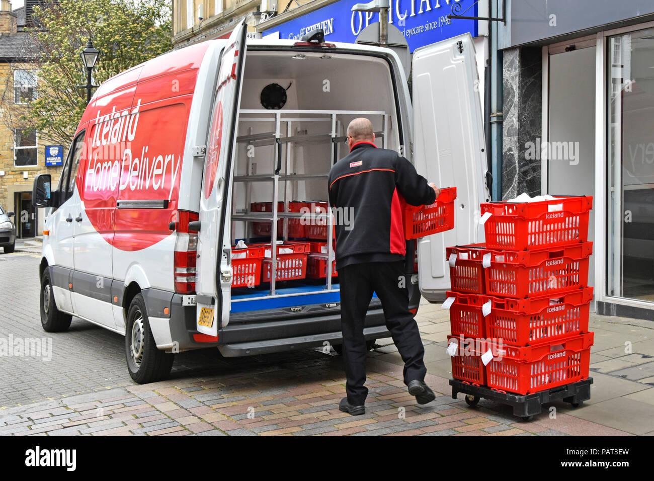 Conductor de la entrega a domicilio van cargando en la calle angosta con la línea de órdenes de compras de alimentos de supermercado Iceland tienda en Hexham Northumberland Inglaterra Imagen De Stock