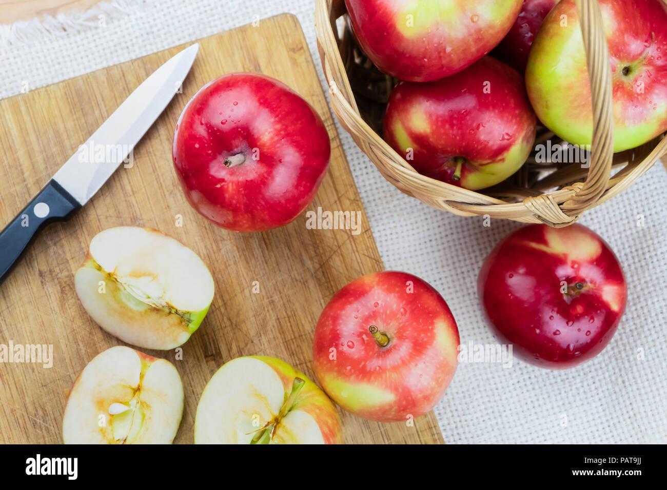 Vista superior de maduras manzanas jugosas sobre mesa de madera rústica. Casa cultivan manzanas orgánicas y la cuchilla, tomada desde arriba Foto de stock