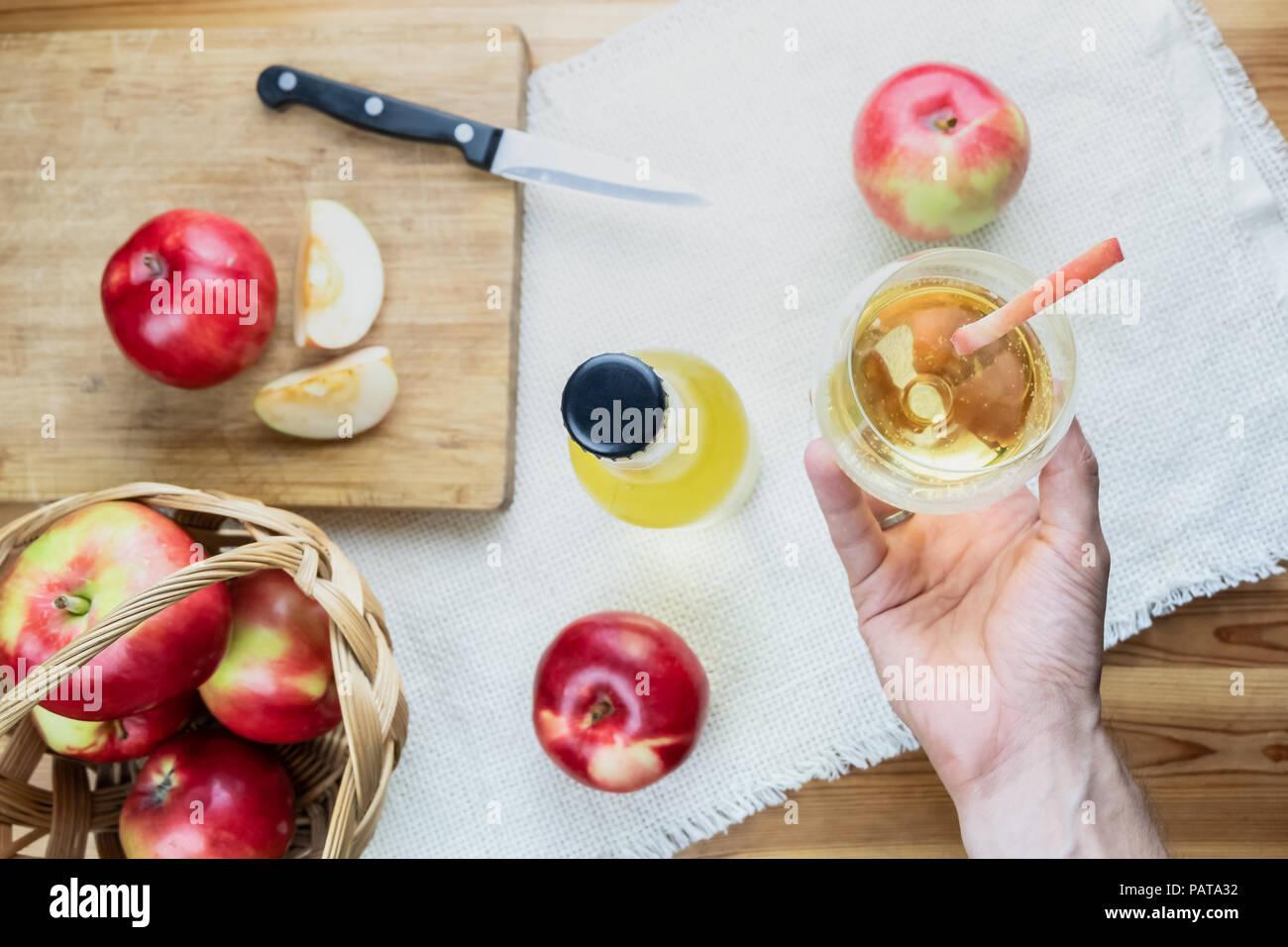 Vista superior de maduras manzanas jugosas y copa de sidra bebida sobre mesa de madera rústica. Punto de vista de mano sosteniendo un vaso de sidra casera y crecer localmente Imagen De Stock