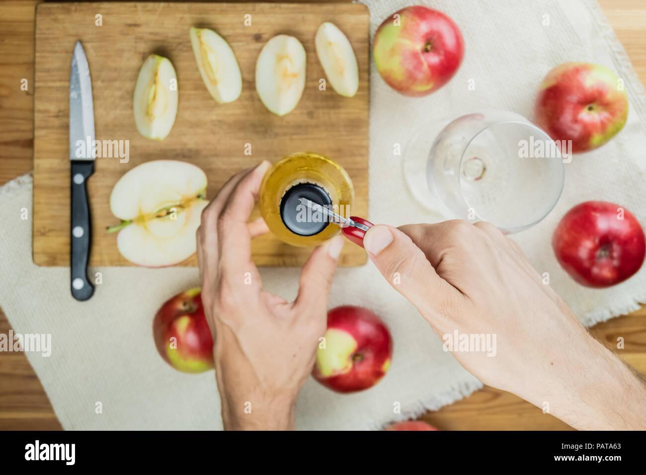Abrir una botella de beber sidra de manzana, vista superior. Punto de vista de la mano con un abrelatas, preparando una copa de sidra en la mesa de madera rústica con maduras appl Imagen De Stock