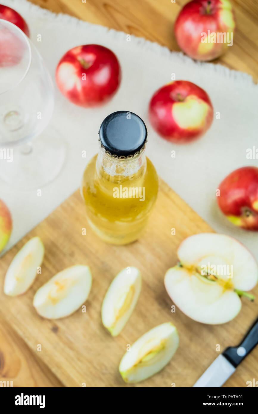 Vista superior de la botella de sidra de manzanas maduras y mesa de madera rústica. Vidrio y botella de sidra casera y manzanas orgánicos cultivados localmente, tomada desde arriba Imagen De Stock