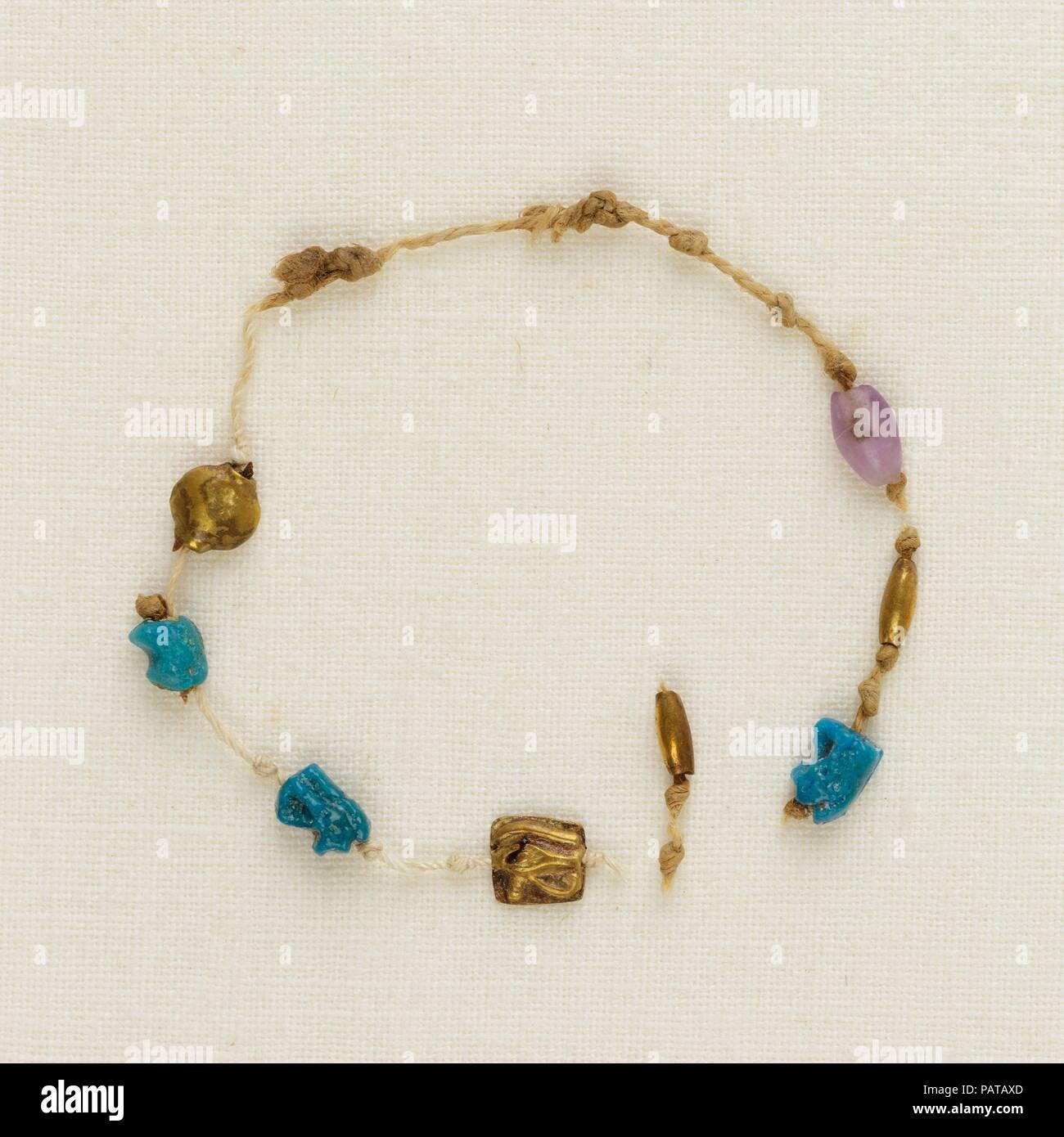 """Brazalete con 4 ojos wedjat, 2 cordones de barril y 1 cordón de acacia. Dimensiones: Diam. ca. 3,8 cm (1 1/2""""). Dinastía: Dinastía tardía 21. Fecha: ca. 1000-945 A.C. Uno de los cinco brazaletes encontrado alrededor de la muñeca derecha de la momia Henettawy, este es un solo hilo de cordoncillo. Encuerda a intervalos a lo largo del Strand fueron cuatro ojos wedjat amuletos, tres de loza y uno de oro; una de oro y una amatista; y un cordón de barril de oro Cordón de acacia. El cable estaba roto, por lo que el orden original de los abalorios y amuletos es incierto. Los ojos wedjat representan el sanado el ojo del dios halcón Horus, un potente sym Foto de stock"""