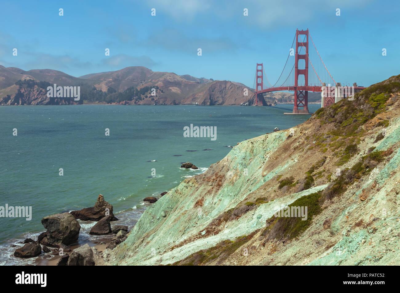 Verde-azulado serpentinite exclusivo de Marshall Beach, con el puente Golden Gate en el fondo, San Francisco, California, Estados Unidos. Imagen De Stock