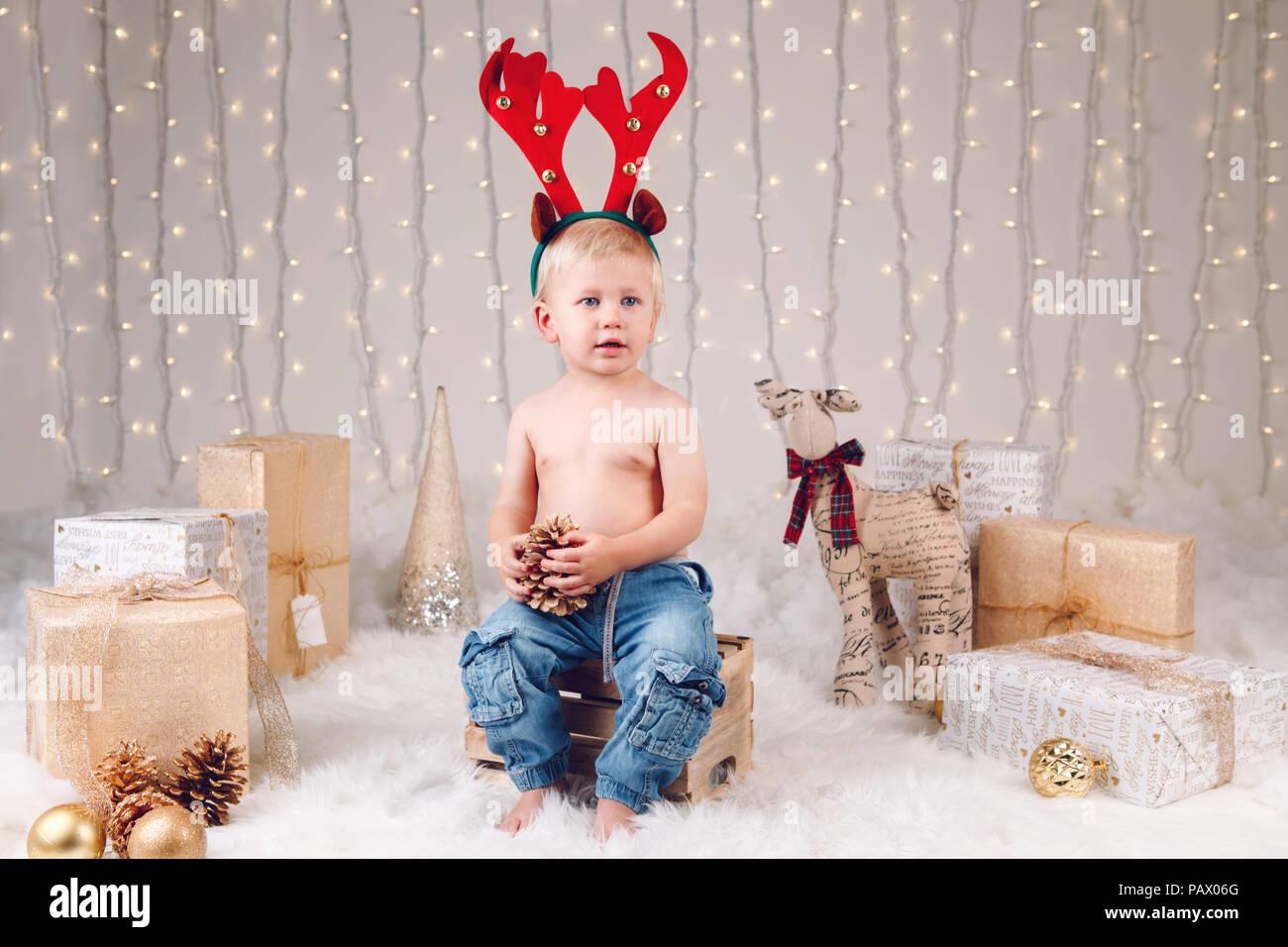 Retrato de niño caucásicos blancos con venados moose diadema cuernos  celebrando la Navidad o Año Nuevo 9a69f3ebeb0