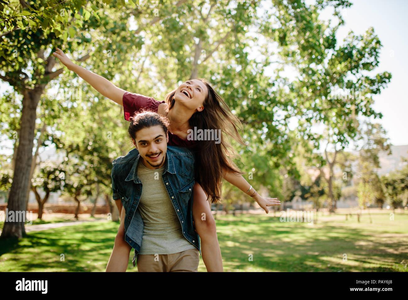 Apuesto joven dando a su novia un viaje combinado en el parque. Par aprovechar al aire libre. El hombre lleva una mujer con una amplia propagación de armas. Imagen De Stock