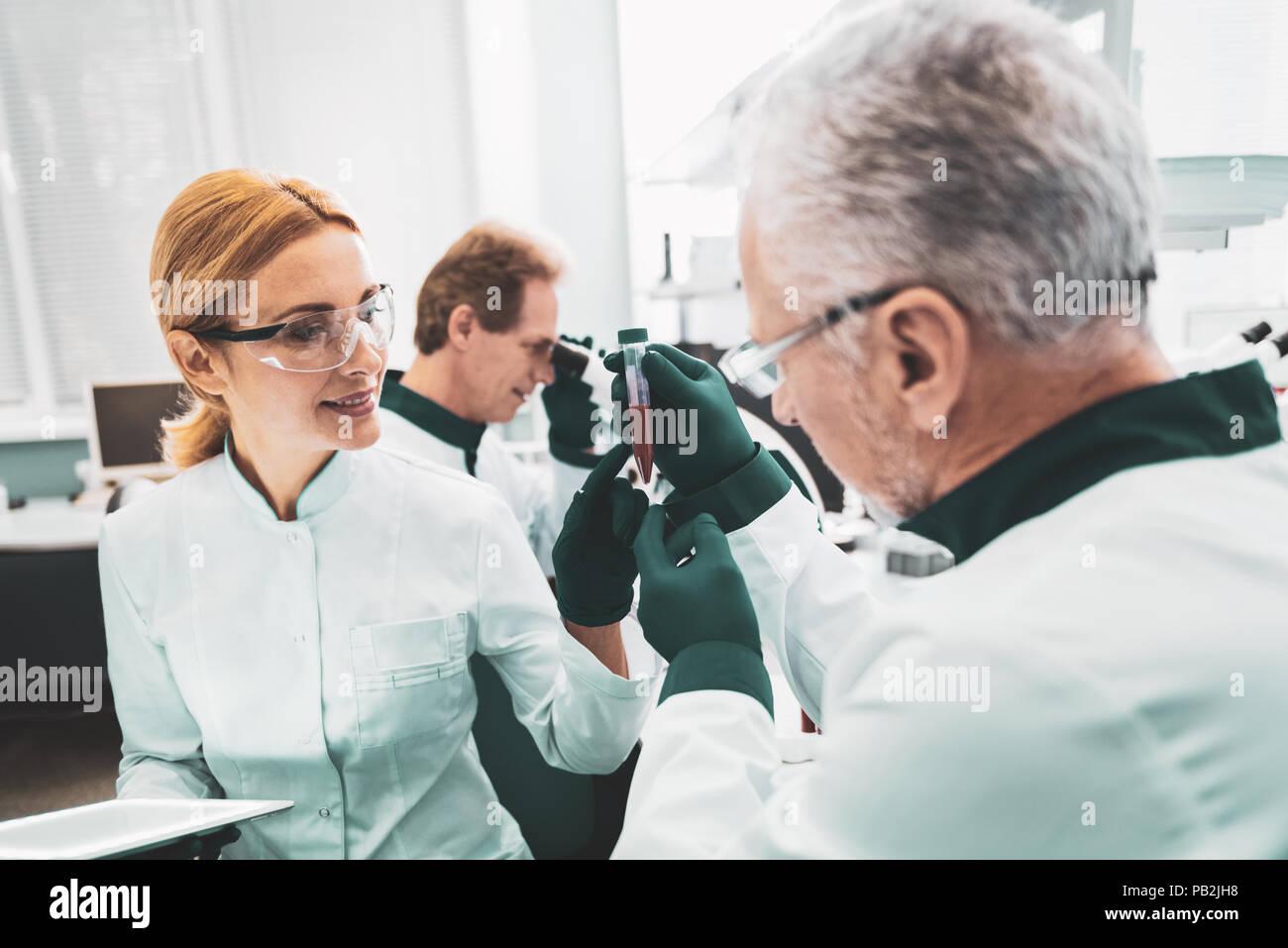 Ayudante de química cooperando con su asesor científico Foto de stock
