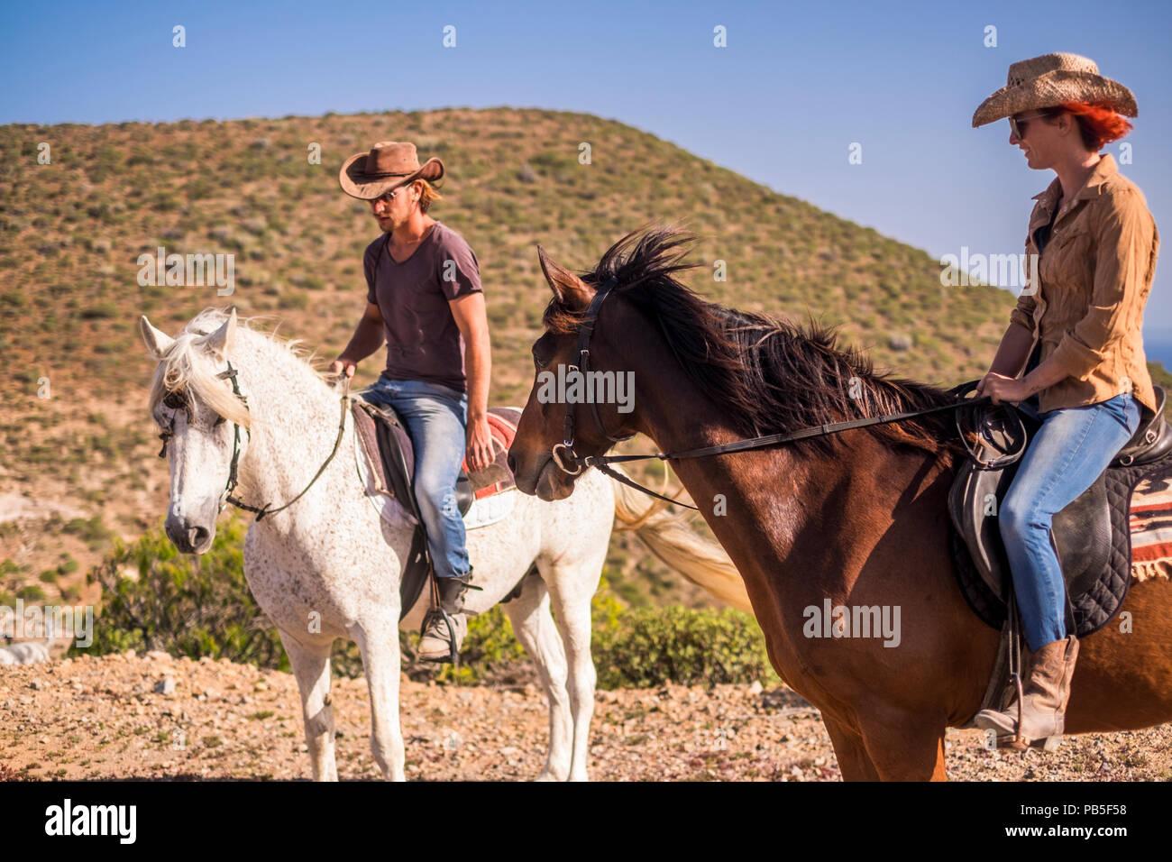 Par de jinete al hombre y a la mujer con Brown y caballos blancos ir y disfrutar de la actividad de ocio al aire libre en excursión viajar a las montañas. moderna cowbo Imagen De Stock