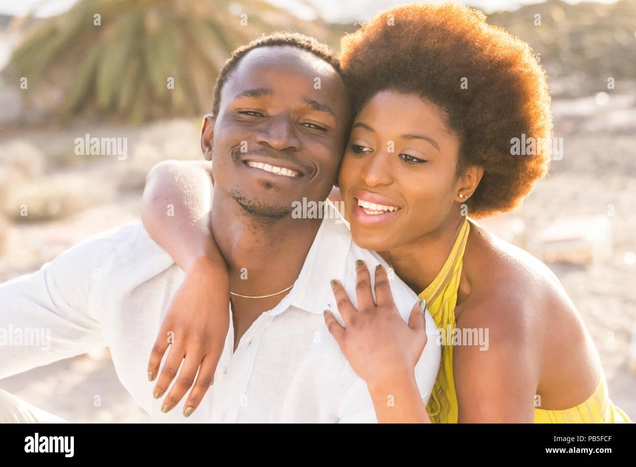 Hermosa raza negra africana feliz pareja en el amor o la amistad permanecer caminando juntos abrazados con grandes smilies bajo el sol del verano en vaca Imagen De Stock