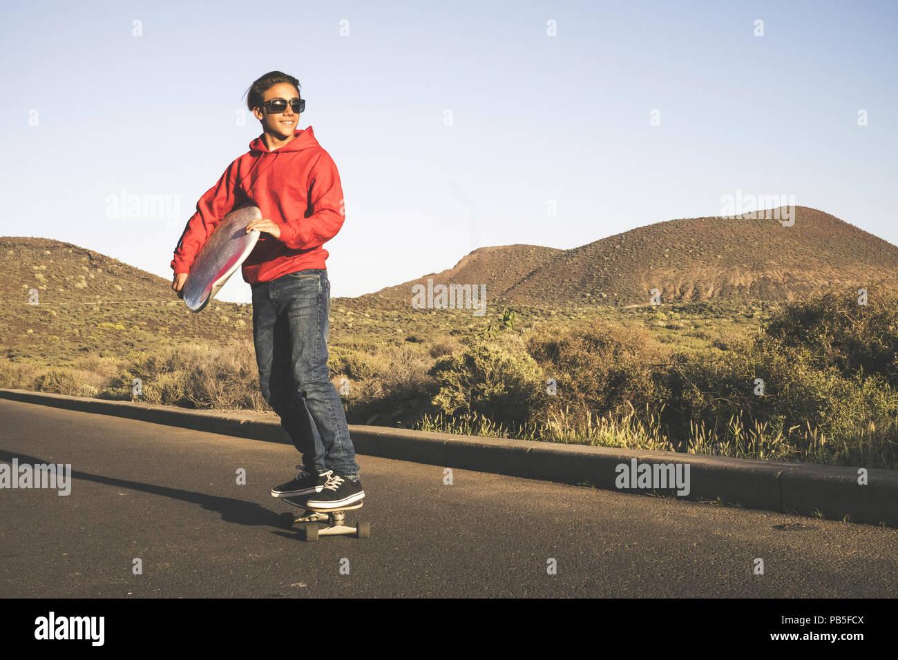 Hermoso macho joven adolescente, ir a la playa con el monopatín llevar una tabla de surf para la actividad de agua en el verano. ocio al aire libre peo para Niza Foto de stock