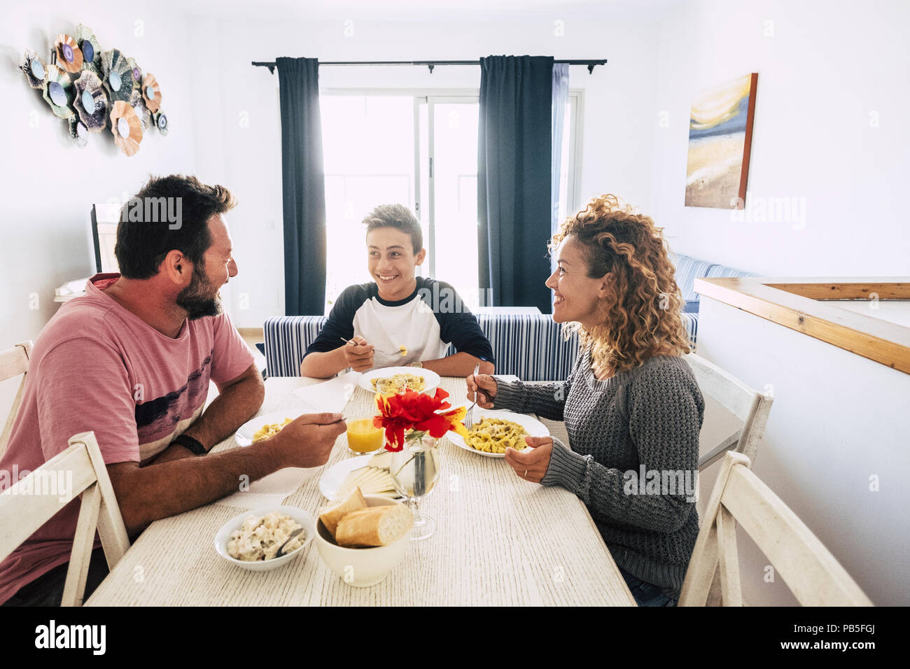 Feliz y alegre familia caucásico almorzando juntos en casa. pared blanca y brillante imagen. juntos, disfrutar el día sonriendo y mirando con amor Imagen De Stock