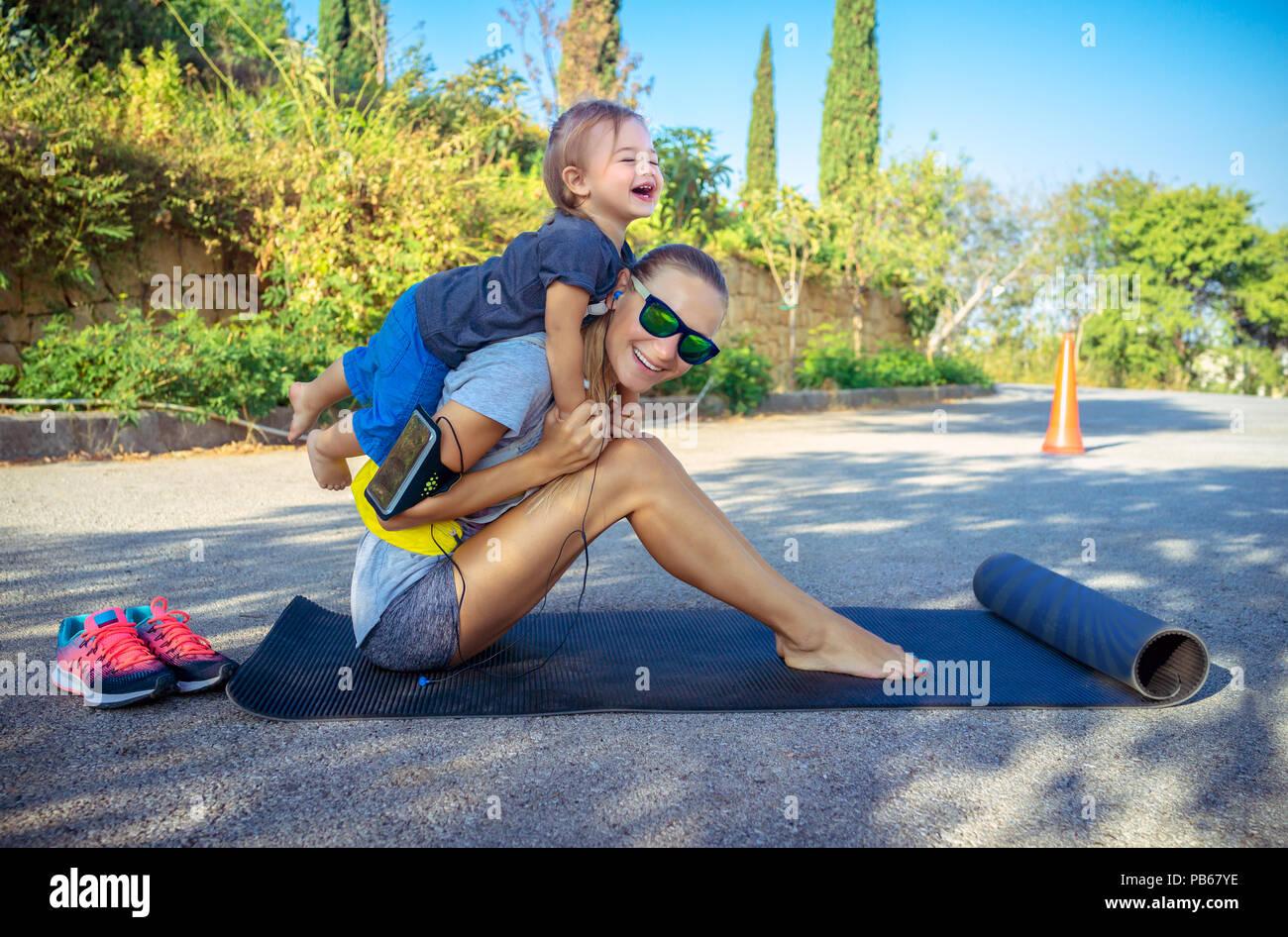 Una vida familiar sana, lindo alegre Baby Boy juega piggy back y le ayudará a hacer estiramientos, hermosa mujer con su pequeño hijo haciendo deporte ejercicio Imagen De Stock