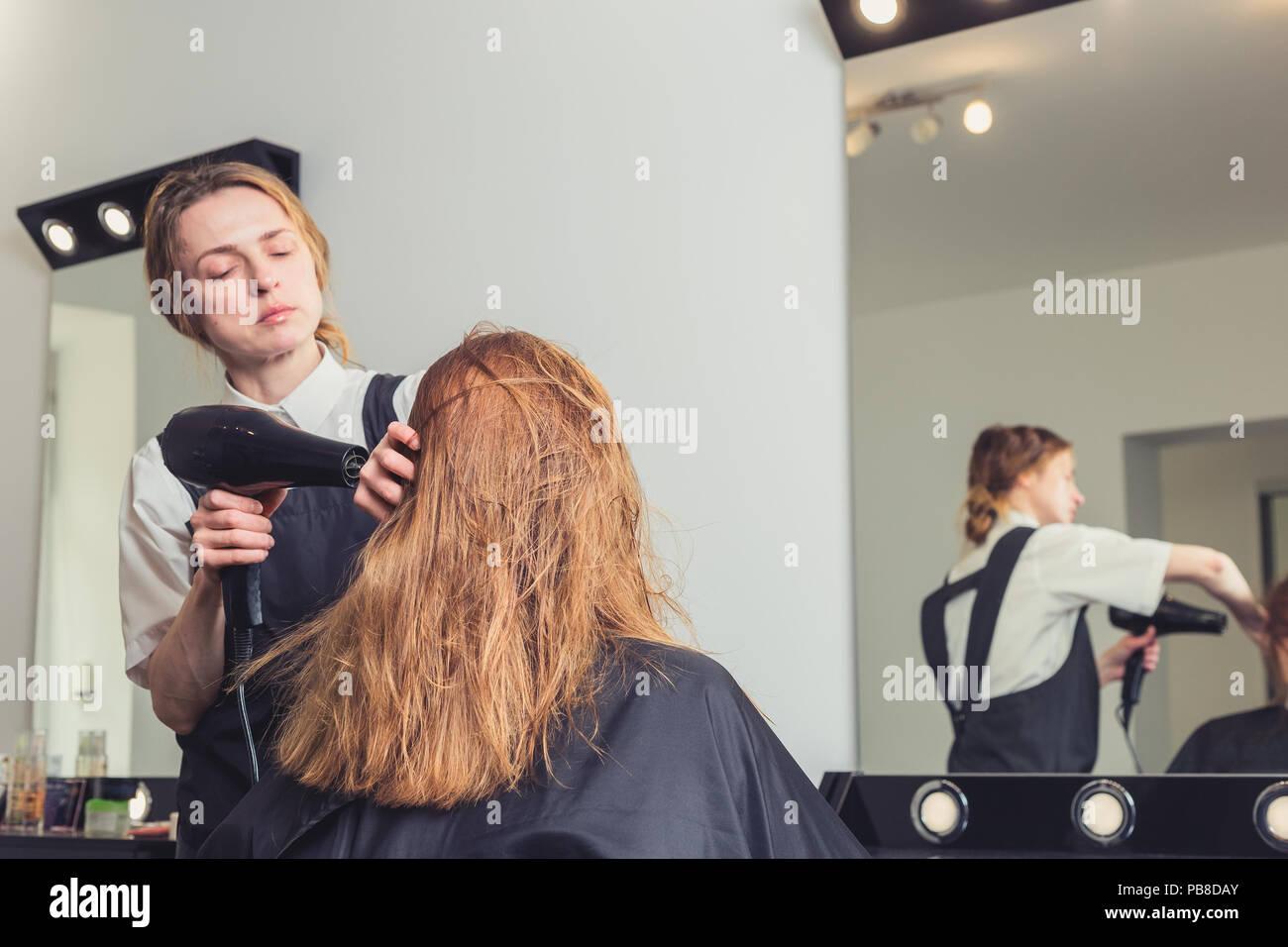 Esteticista golpe de secado el cabello de la mujer en el salón de belleza Foto de stock