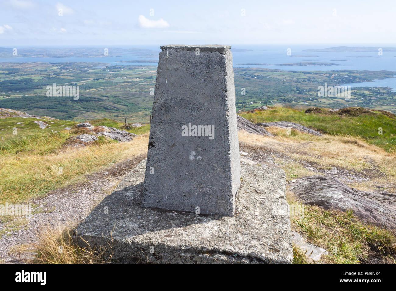 Punto de triangulación en la cumbre del monte Gabriel, West Cork, Irlanda, con vistas de la bahía de agua rugiente más allá. Imagen De Stock