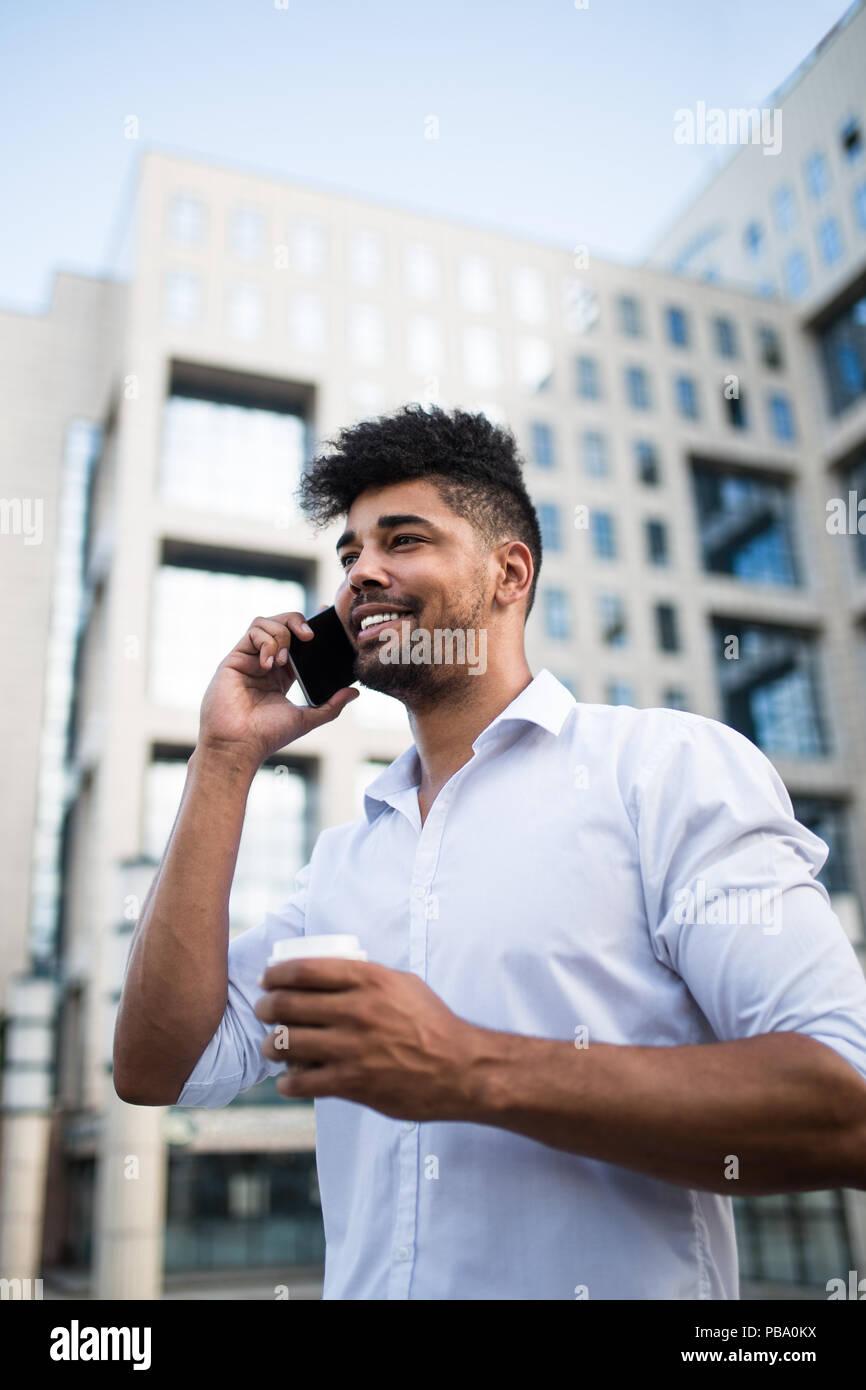 Joven apuesto hombre afro americana de pie delante del enorme edificio moderno de negocios, sonriente, sosteniendo el café para ir y hablar por teléfono móvil. Foto de stock