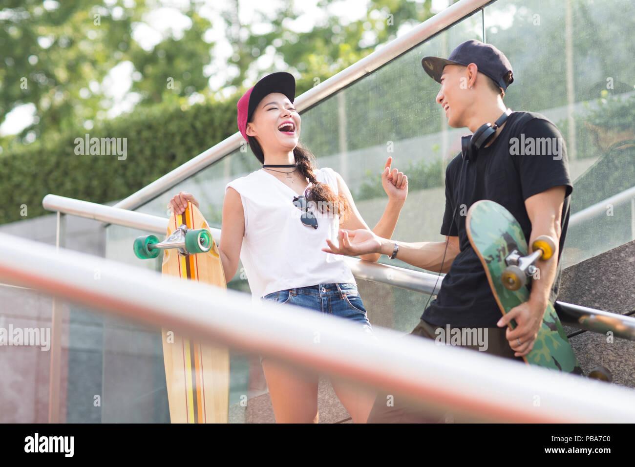 Alegre pareja joven chino con skateboard hablando en las escaleras Imagen De Stock