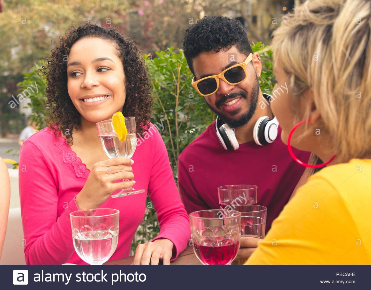 Grupo multirracial de estudiantes teniendo un gran momento en la cafetería al aire libre. Feliz amigos socializar en un partido en el restaurante exterior. Verano caliente, frien Imagen De Stock