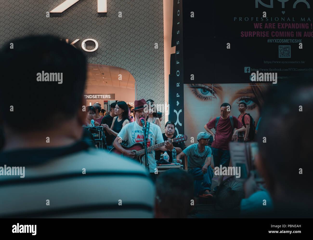 El 28 de julio de 2018, Hong Kong: Mong Kok cultura callejera. La gente ve un músico de calle performance en Sai Yeung Choi Street, Mongkok en Hong Kong. Imagen De Stock