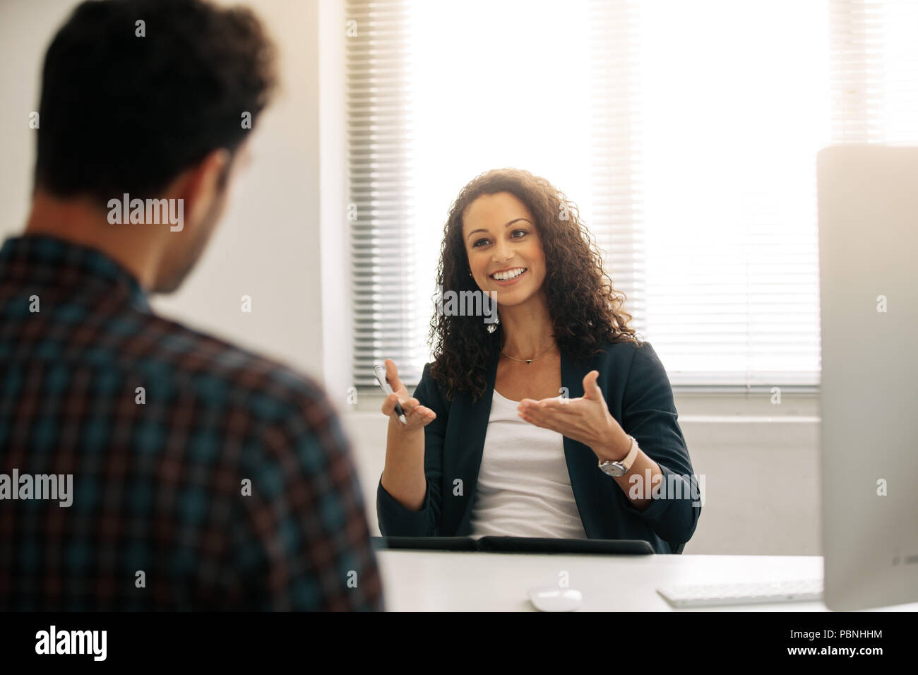 Empresaria discutir ideas de negocios con un socio de negocios en la oficina. Empresaria en una reunión con un empresario en su escritorio en la oficina. Imagen De Stock