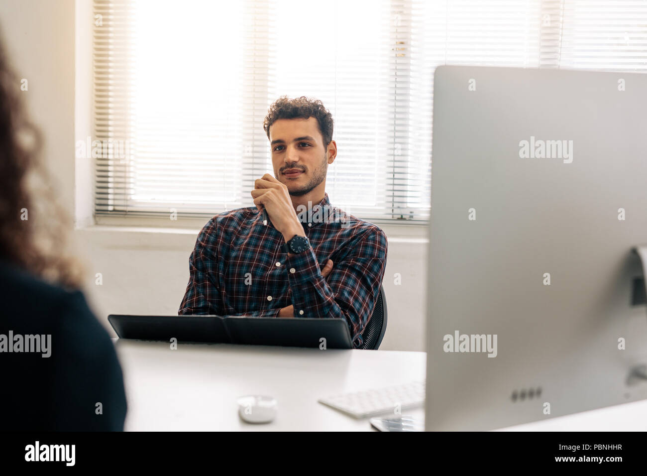 Empresario discutir el trabajo con un socio de negocios sentada en su escritorio en la oficina. Socios de negocios en una reunión en la oficina. Imagen De Stock