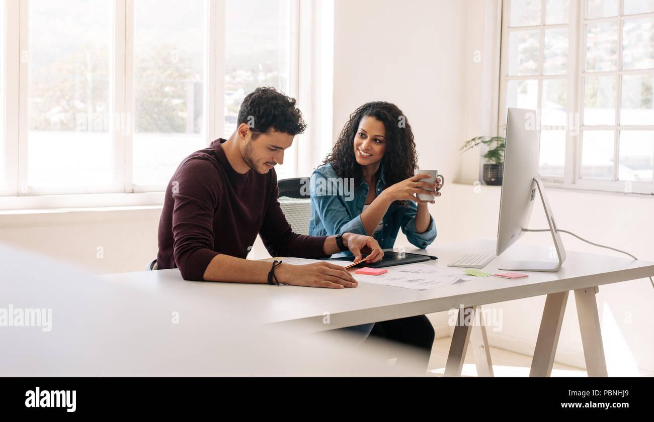 La empresaria sosteniendo una taza de café mirando a su socio de negocios mientras discuten sentados en la mesa de trabajo en la oficina. Imagen De Stock