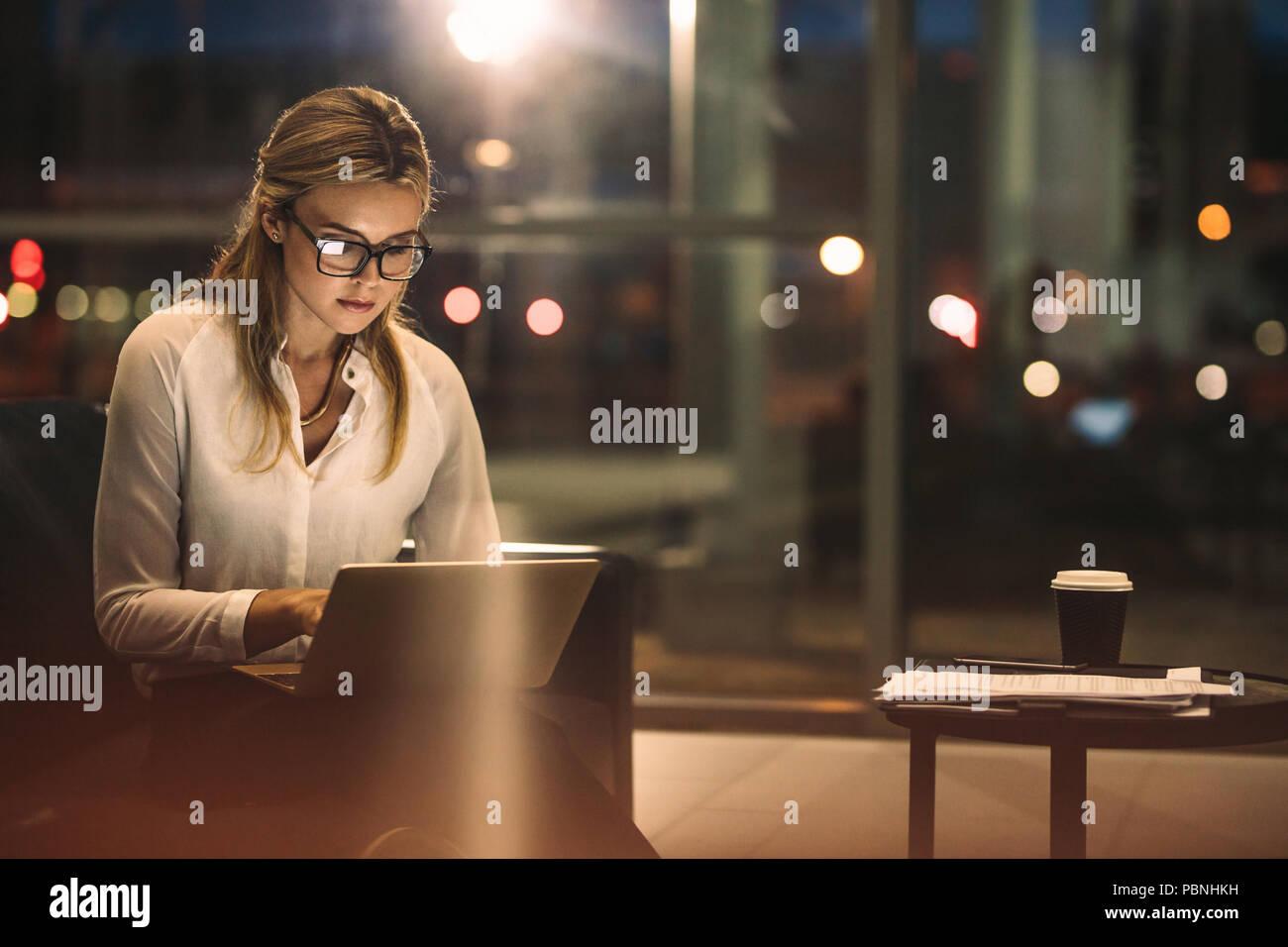 Joven trabajando en el portátil a altas horas de la noche. La empresaria caucásica trabajando horas extras en la oficina para terminar el proyecto dentro de la fecha límite. Imagen De Stock