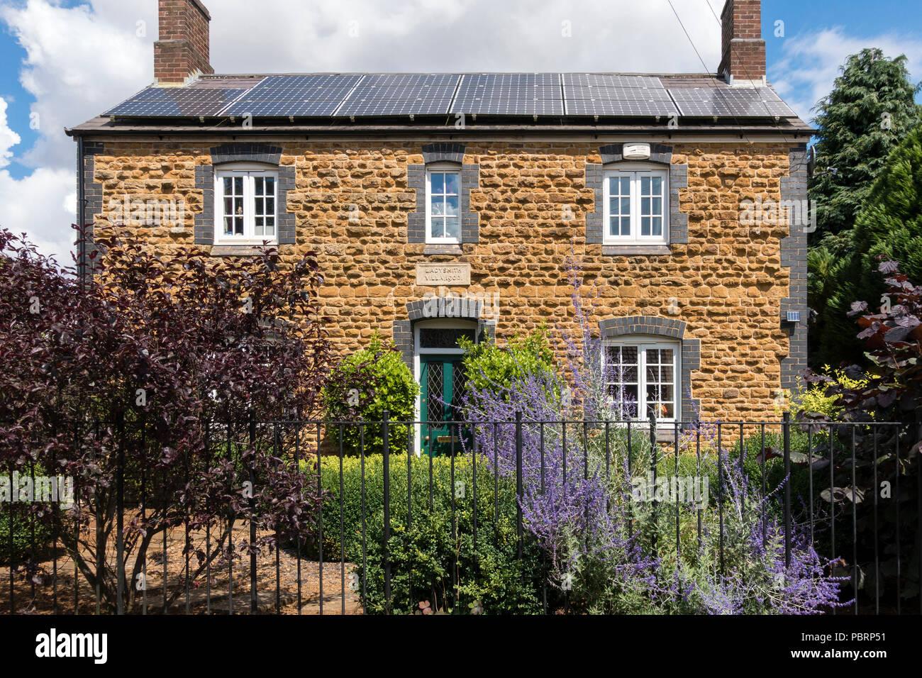 Elevación frontal, Ladysmith Villa, azul antiguo ladrillo y piedra amarilla casa construida con paneles solares en el techo, el C1900, Somerby, Leicestershire, Inglaterra, Reino Unido. Imagen De Stock