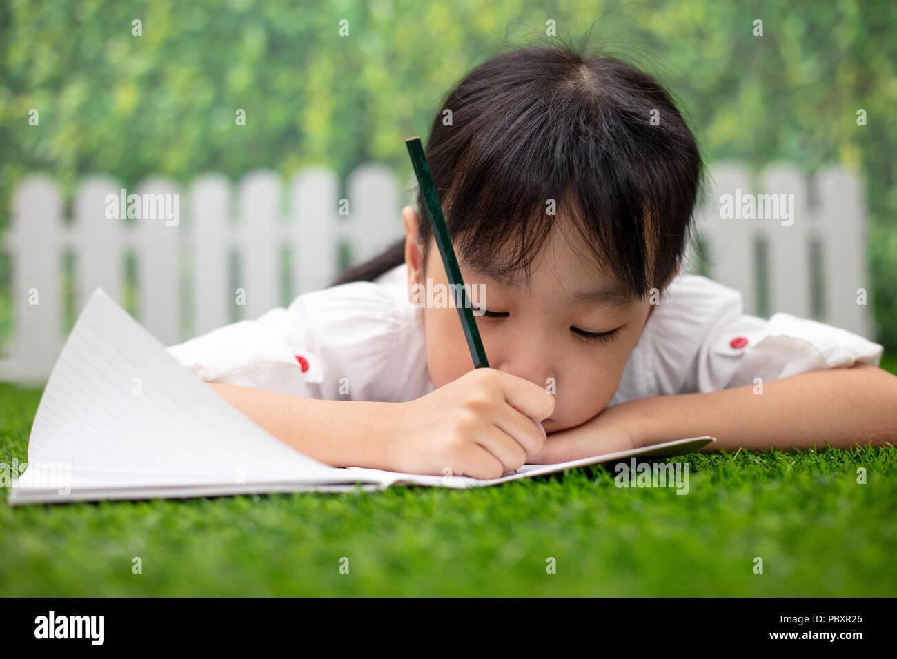 Niña China Asia arrodillado en el césped y hacer los deberes en el parque al aire libre Imagen De Stock