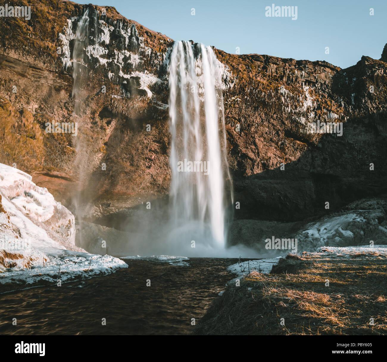 Un paisaje maravilloso de la cascada Seljalandsfoss en Islandia, en un día claro, con el cielo azul y la nieve. Foto de stock