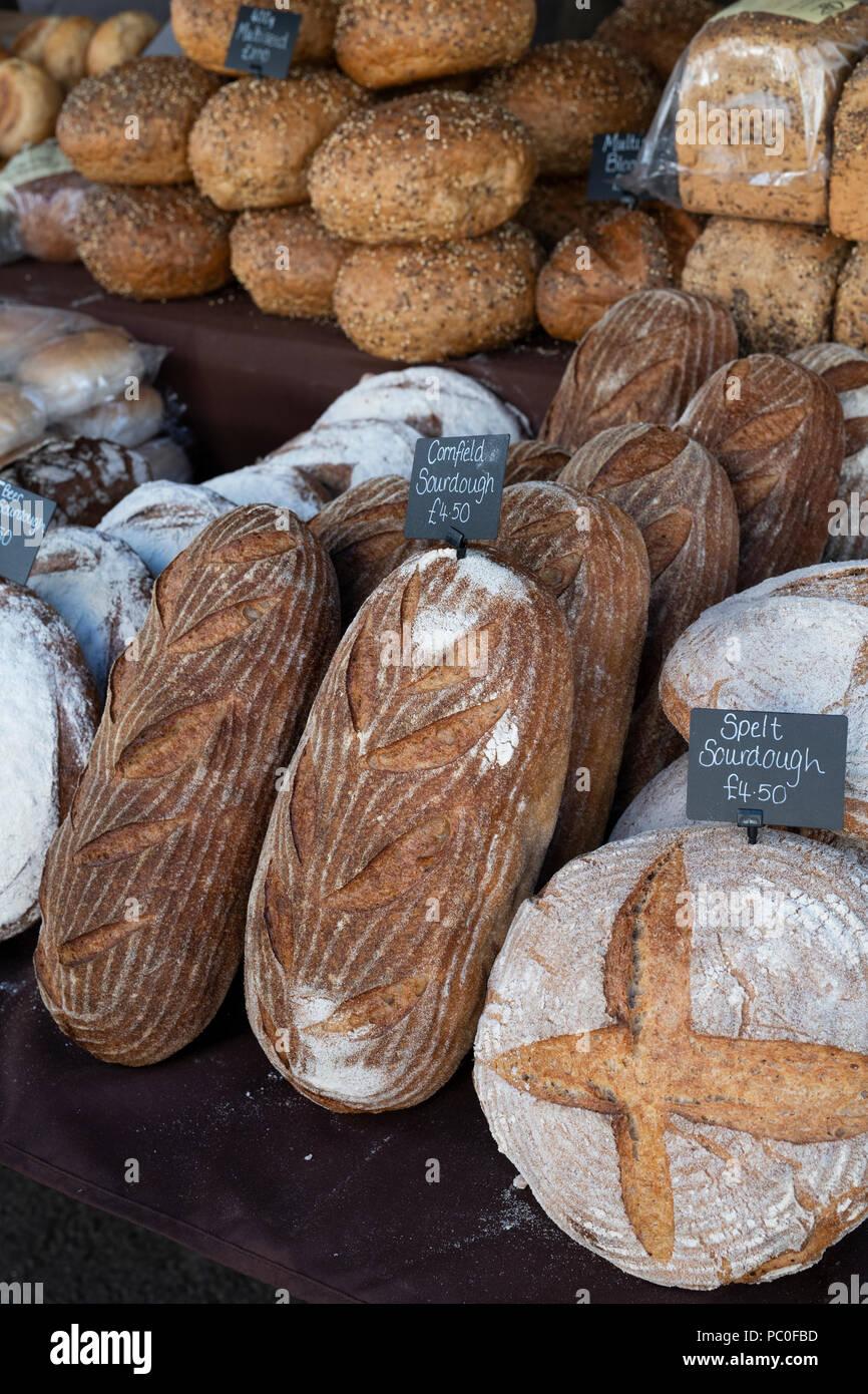 Pan de masa fermentada para la venta en un puesto en un mercado de granjeros. Deddington, Oxfordshire, Inglaterra Imagen De Stock