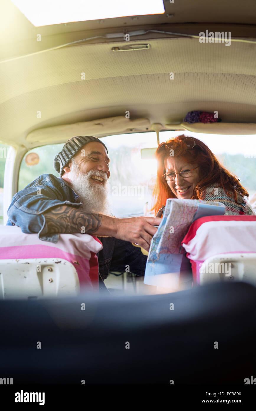 Viejo hipster par sentarse en un coche y mirando un mapa de carreteras Foto de stock