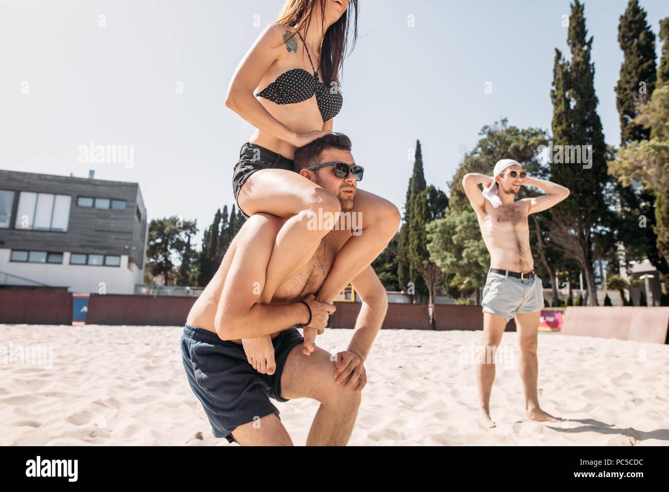 Romántica pareja joven disfrutando de sus vacaciones de verano. Apuesto joven dando piggyback paseo a la novia en la playa. Foto de stock
