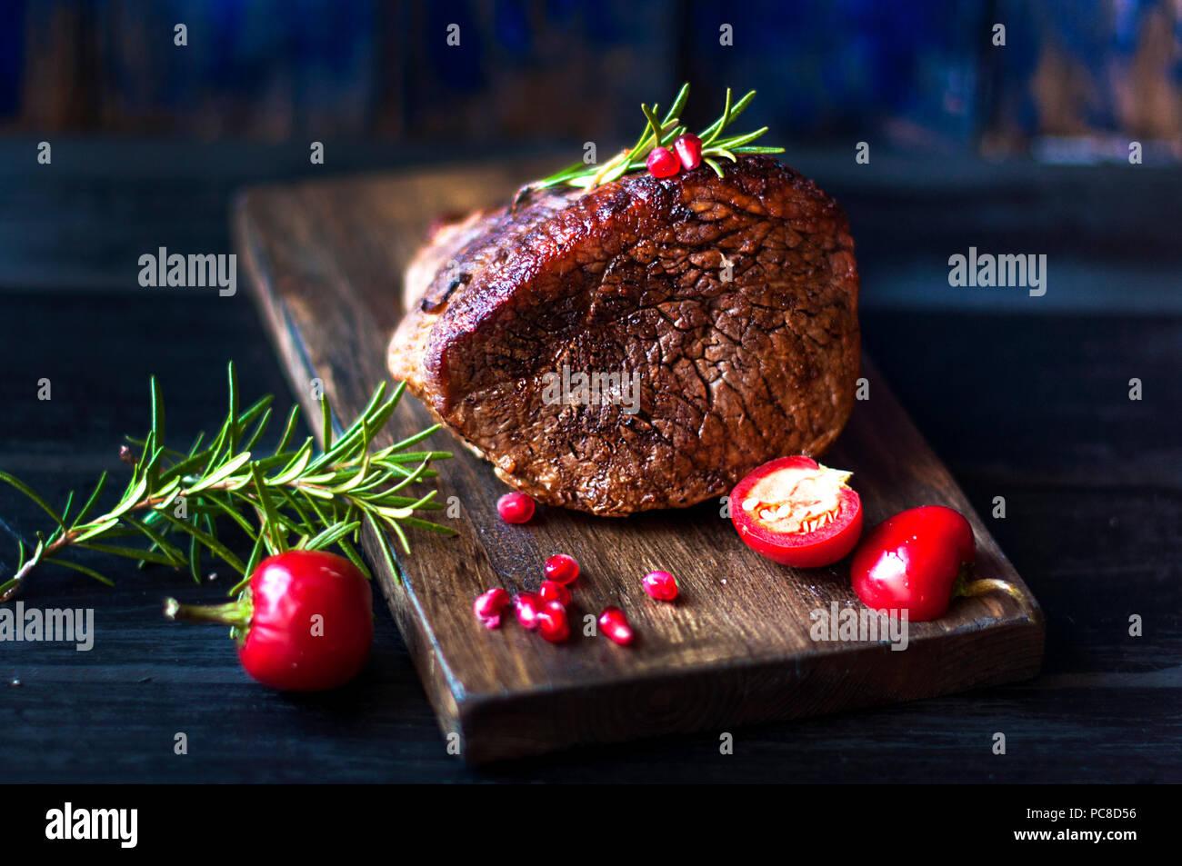 Carne cocida con romero y el pimiento rojo. Filete de ternera. cena para hombres. foto oscura. Fondo negro. La plancha de madera. Imagen De Stock