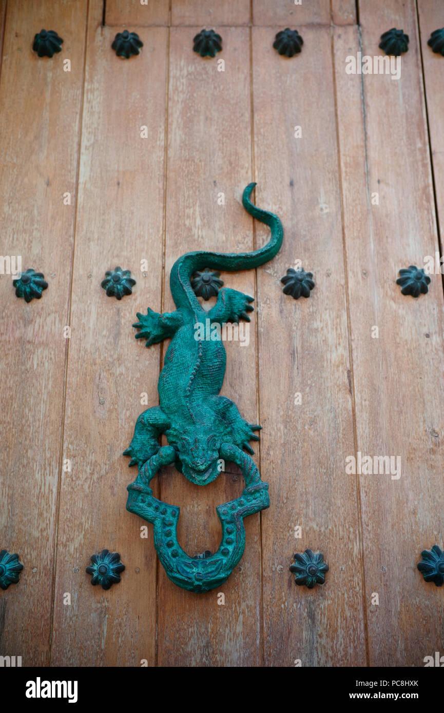 Puerta de hierro esculpido martinete en una antigua puerta de madera. Foto de stock