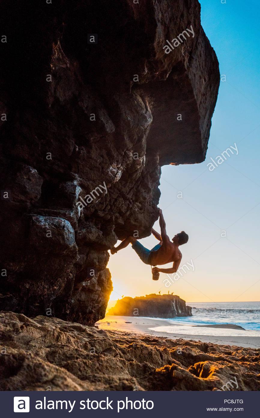 Un hombre trepar rocas en la playa de Oahu. Imagen De Stock