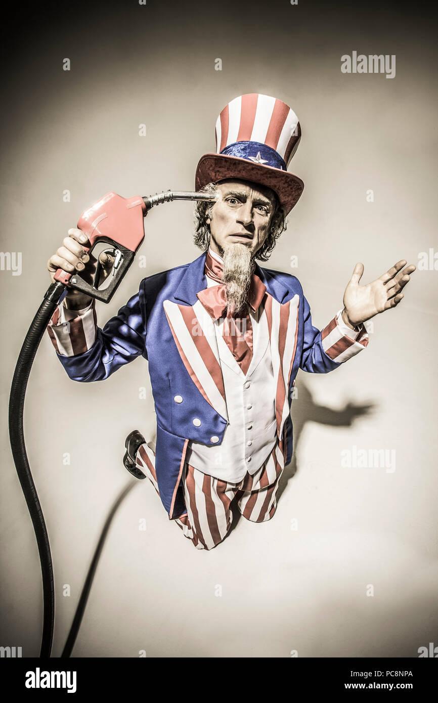El Tío Sam de pie con una bomba de gas nozzel celebró en frente de él. Captura conceptual representando la adicción al petróleo americano / gas / petróleo. Foto de stock