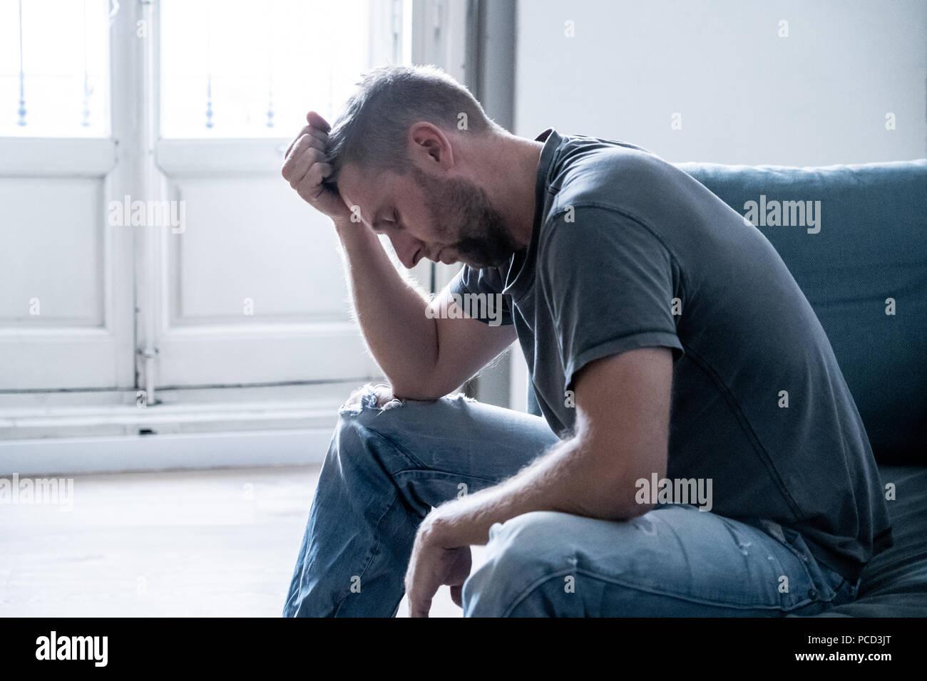 Infeliz deprimido masculino caucásico sentarse y acostarse en el sofá de su sala de estar sintiendo un solitario desesperado. En resaltado desde el trabajo, ansiedad, descorazonado y de Foto de stock