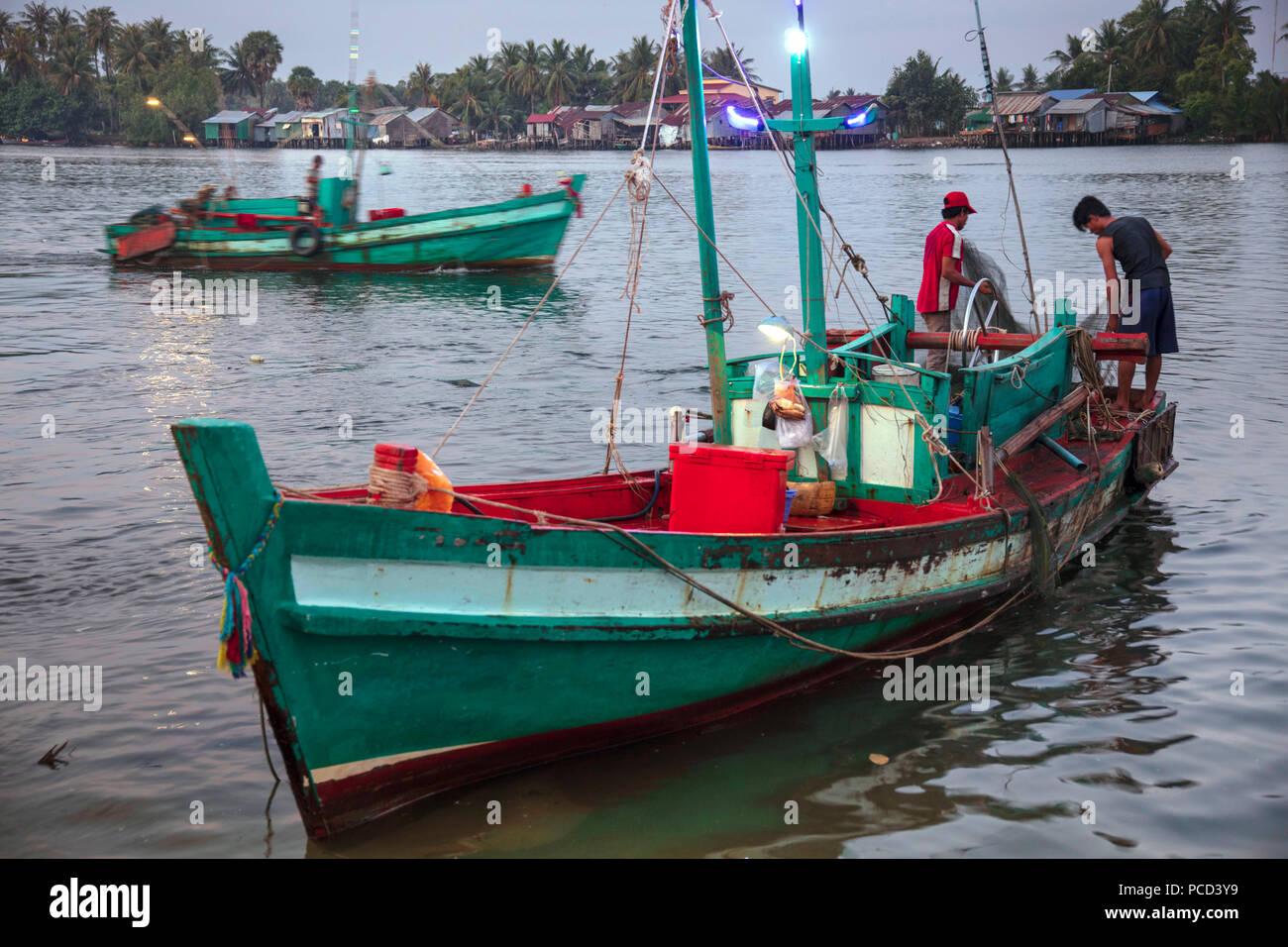 Barco de pesca en la mañana mercado de pescado, en las orillas del río Chhu Preaek Tuek en Kampot town, Camboya, Indochina, en el sudeste de Asia, Asia Foto de stock