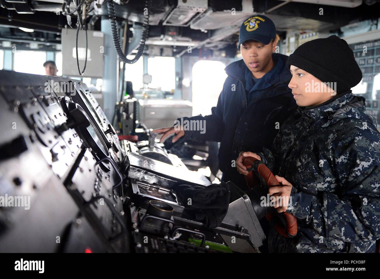 Las aguas al oeste de la península de Corea (18 de marzo de 2013) Boatswain's Mate de 3ª clase Brittany Chiles trenes Seaman Jessica Canas mientras le mans el timón a bordo de la clase Arleigh Burke de misiles guiados destructor USS McCampbell (DDG 85). McCampbell es parte de Destroyer Squadron 15, desplegadas a Yokosuka, Japón, y se están llevando a cabo para realizar el ejercicio bilateral Foal Eagle 2013 nación aliada con la República de Corea en apoyo de la seguridad regional y la estabilidad de la región del Pacífico Indo-Asia. Foto de stock