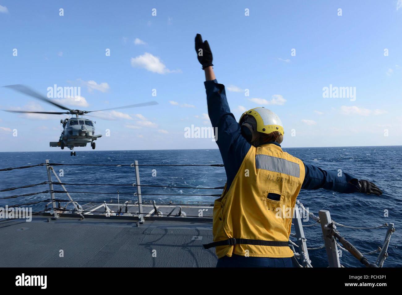 Océano Pacífico (4 de marzo de 2013) Boatswain's Mate de 3ª clase Brittany Chiles señales a un SH-60B Sea Hawk helicóptero mientras aterriza en la cubierta de vuelo a bordo de la clase Arleigh Burke de misiles guiados destructor USS McCampbell (DDG 85). McCampbell es parte del escuadrón destructor15, desplegadas a Yokosuka, Japón, y está en marcha para realizar ejercicio Foal Eagle 2013 nación aliada con la República de Corea en apoyo de la seguridad regional y la estabilidad de la región Asia-Pacífico. Foto de stock