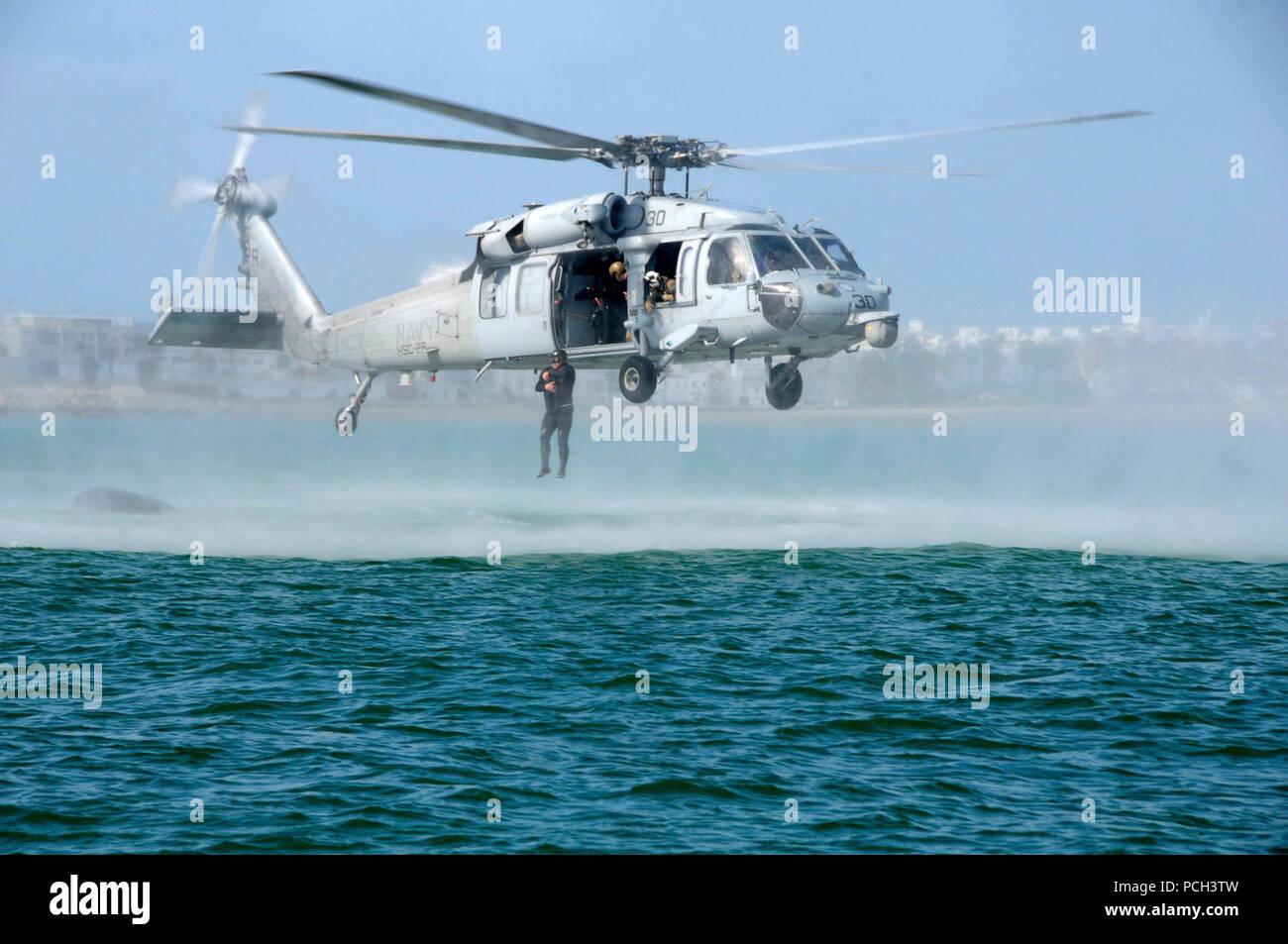La estación naval de Rota, España (5 de marzo de 2015), un marino español expulsa de la Marina SH-60 Sea Hawk helicóptero asignado a las ballenas de dragón de mar escuadrón de helicópteros de combate (HSC) helicóptero 28 durante la capacitación en suspensión de cuerda rota, España. La formación es una evolución conjunta entre la eliminación de artefactos explosivos EODMU unidad móvil (8), el desprendimiento de Rota, y los infantes de marina española. Imagen De Stock