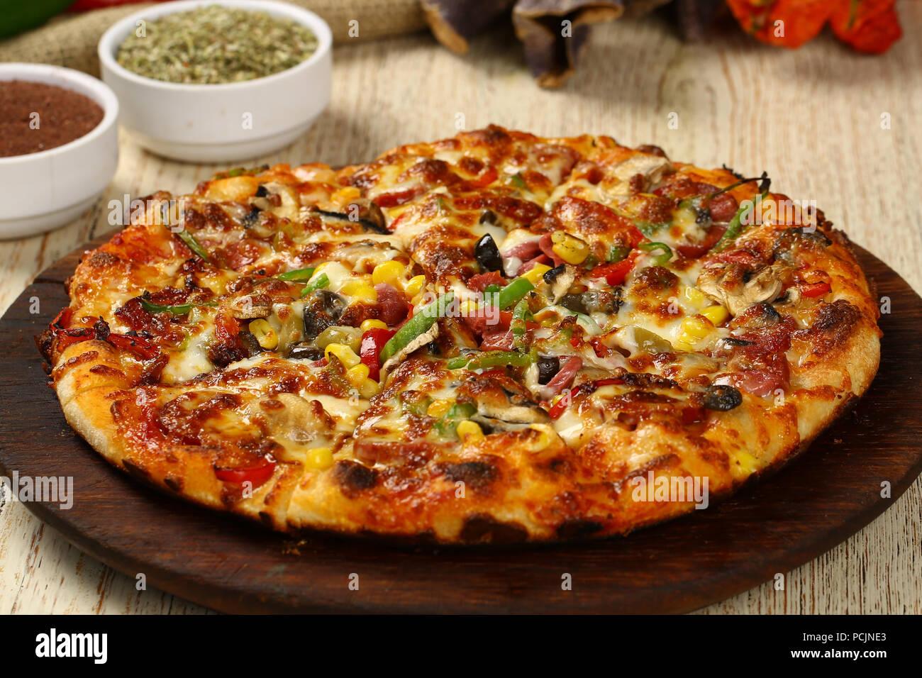 Deliciosa pizza italiana sobre la tabla de madera Imagen De Stock