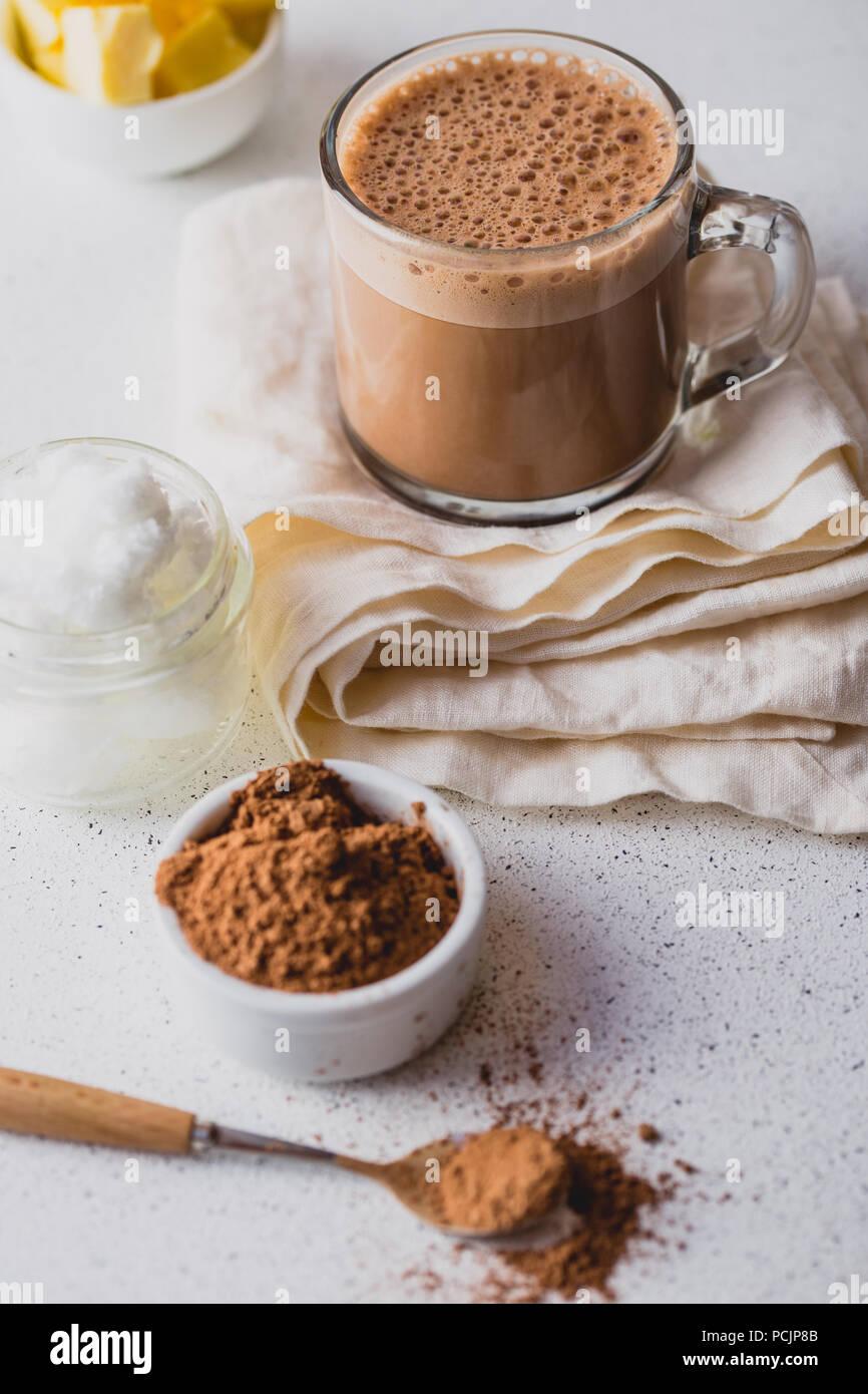Chalecos cacao. Ceto dieta cetog�ica bebida caliente. Cacao mezclado con aceite de coco y la mantequilla. Taza de cacao a prueba de balas y los ingredientes sobre fondo blanco. Imagen De Stock