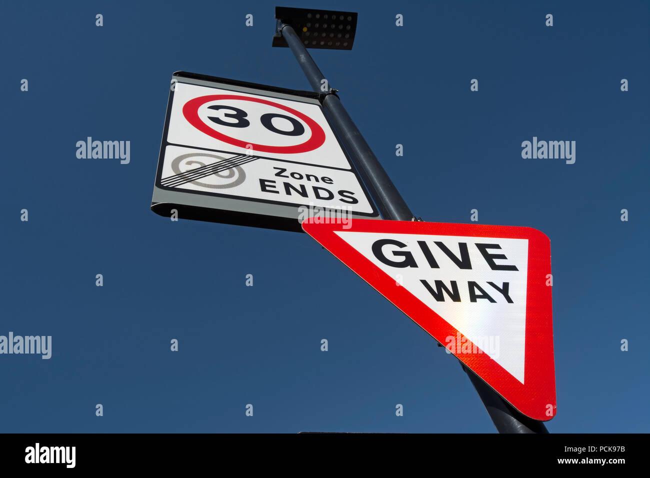 British señales indicando ceder y el inicio de un límite de velocidad de 30 mph y el final de una zona de límite de velocidad de 20mph Foto de stock