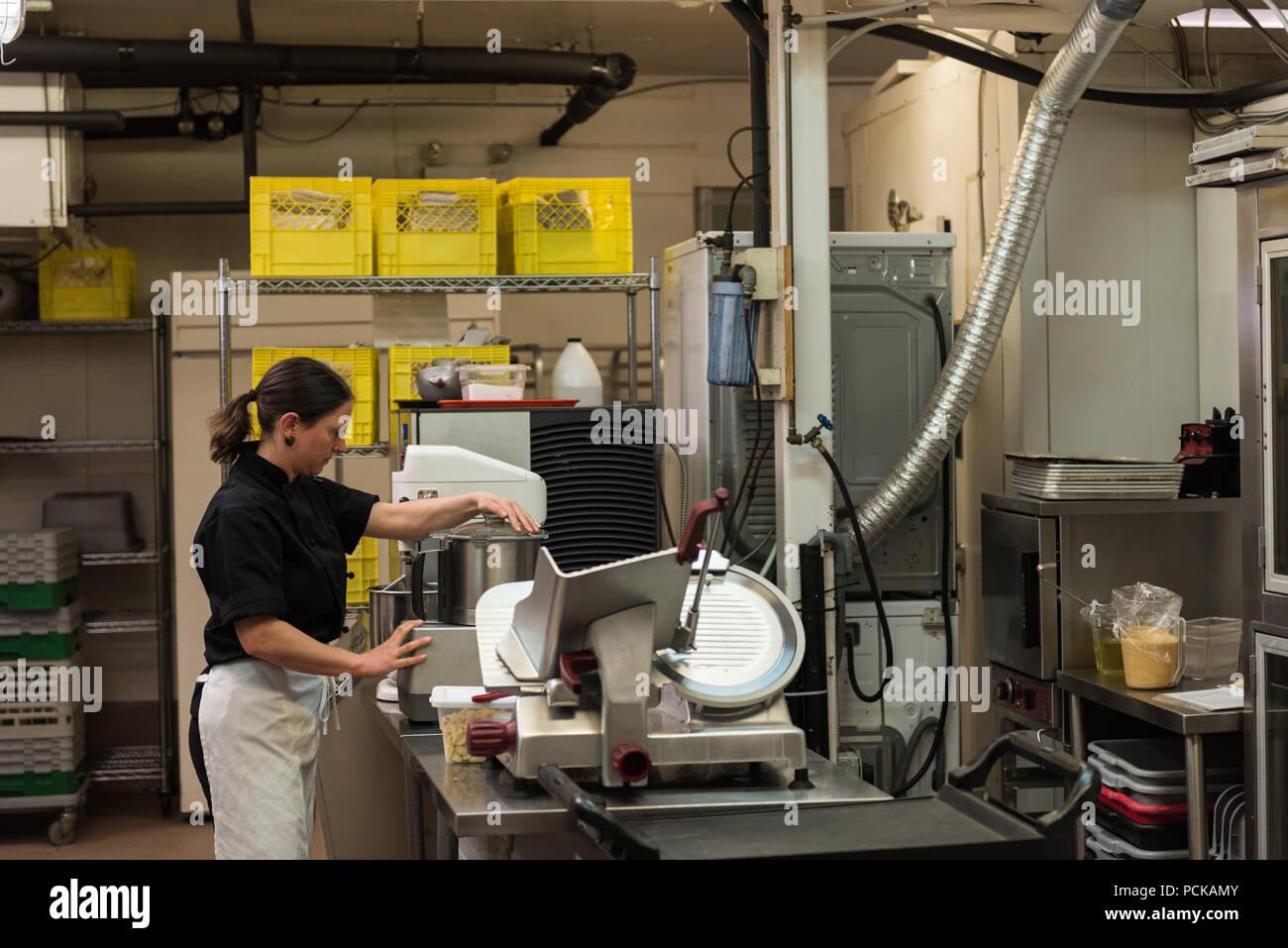 Chef utilizando una muela en una cocina comercial Imagen De Stock