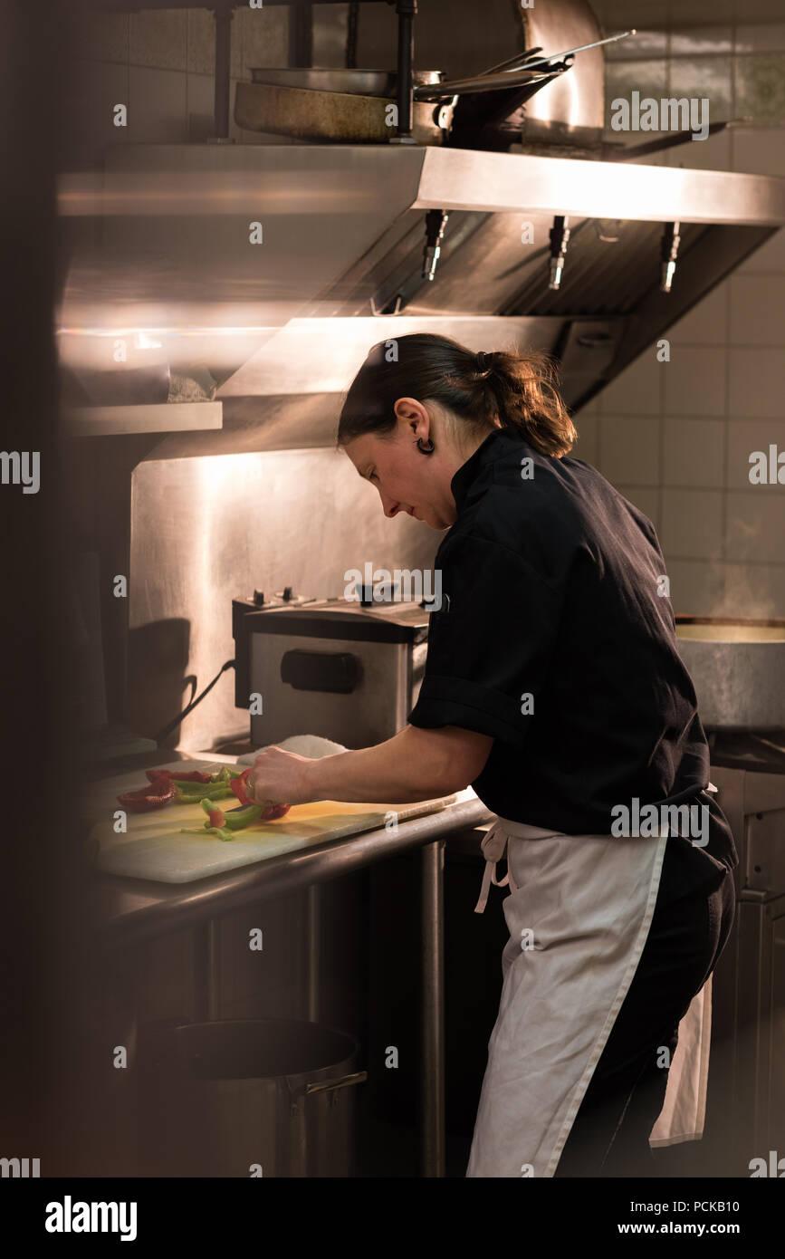 Chef picar verdura en la cocina comercial Imagen De Stock