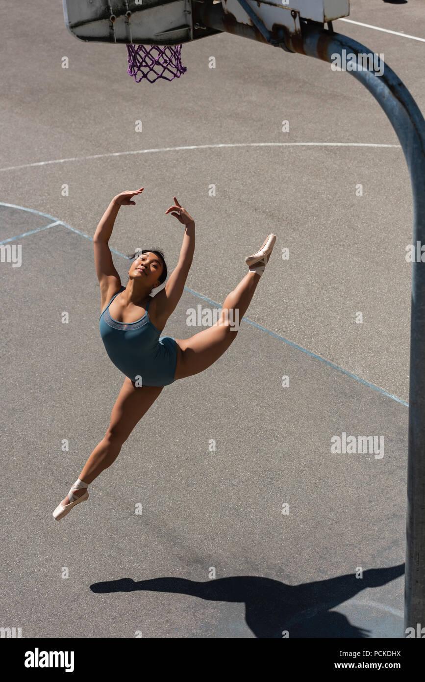 Bailarina de ballet femenino bailando en la cancha de baloncesto Imagen De Stock