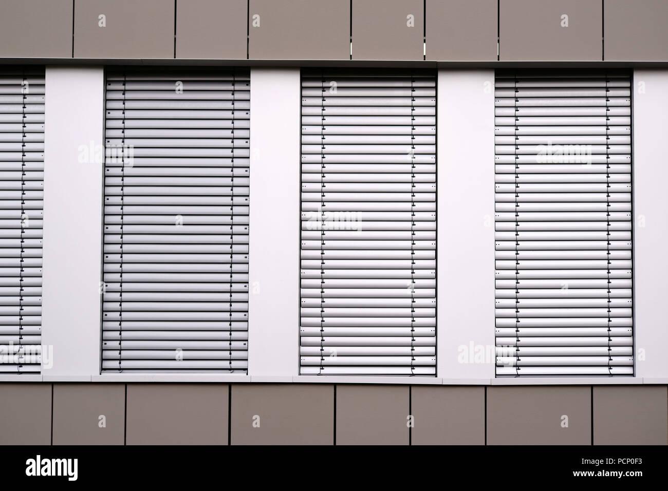 e0f65251b7 La moderna fachada de un edificio de oficinas con filas de ventanas y  persianas de metal